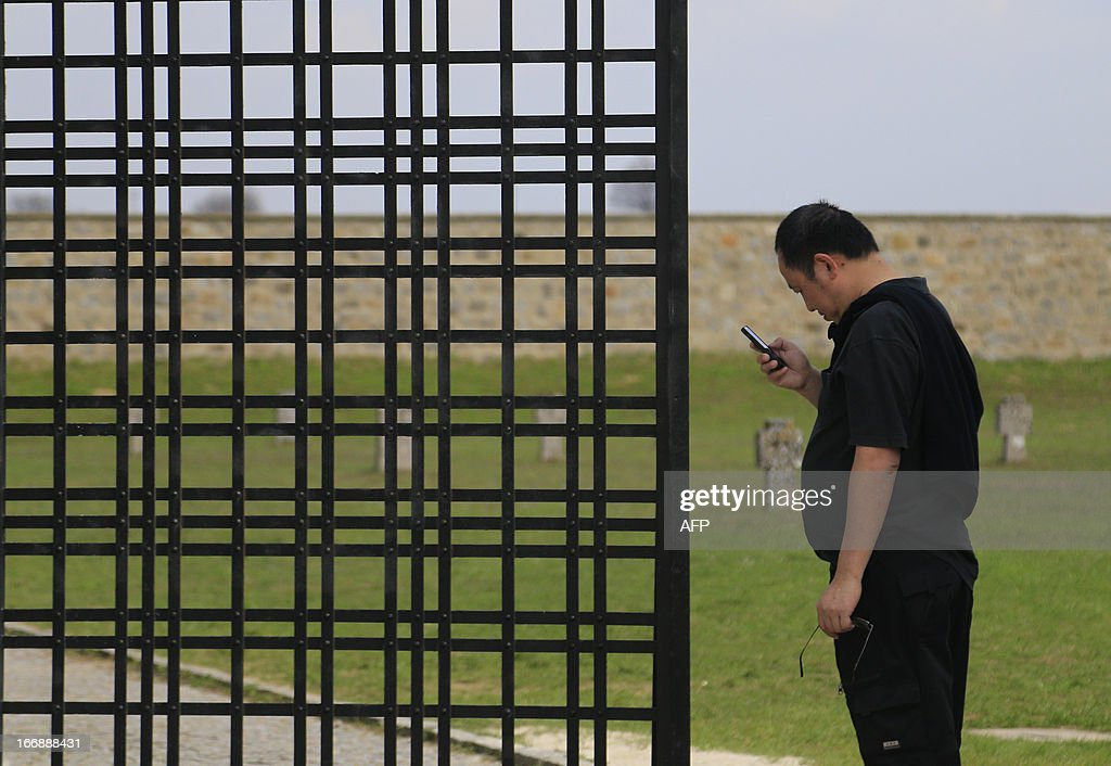 A visitor checks his mobile at the World War II concentration camp of Mauthausen, on April 17, 2013.