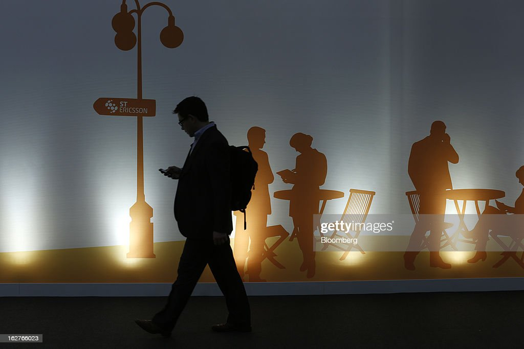 A visitor checks his mobile phone as he passes a sign outside the ST-Ericsson AB pavilion at the Mobile World Congress in Barcelona, Spain, on Tuesday, Feb. 26, 2013. The Mobile World Congress, where 1,500 exhibitors converge to discuss the future of wireless communication, is a global showcase for the mobile technology industry and runs from Feb. 25 through Feb. 28. Photographer: Simon Dawson/Bloomberg via Getty Images