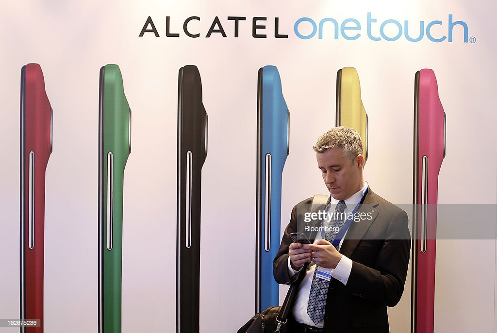 A visitor checks his smartphone beside an advertisement for the Alcatel-Lucent One Touch smartphone at the Mobile World Congress in Barcelona, Spain, on Monday, Feb. 25, 2013. The Mobile World Congress, where 1,500 exhibitors converge to discuss the future of wireless communication, is a global showcase for the mobile technology industry and runs from Feb. 25 through Feb. 28. Photographer: Simon Dawson/Bloomberg via Getty Images