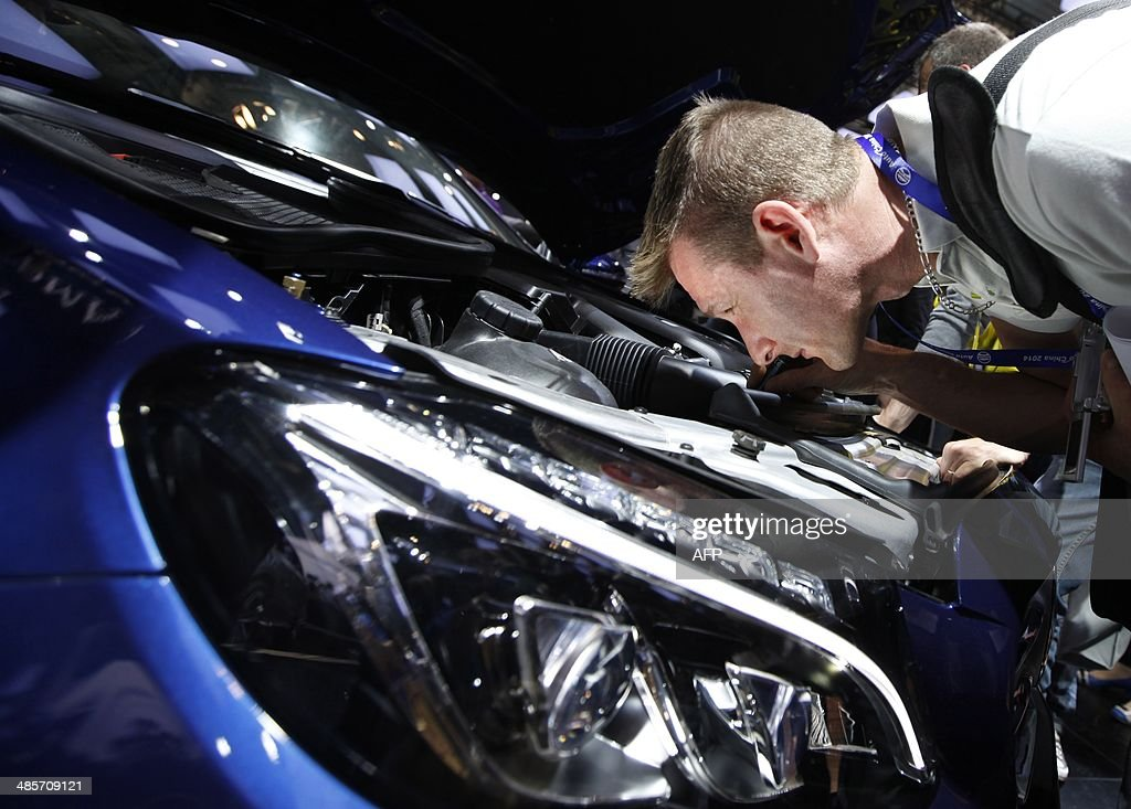 A visitor checks out a McLaren car on display at the China International Exhibition Center new venue during the 'Auto China 2014' Beijing International Automotive Exhibition in Beijing on April 20, 2014. Leading automakers are gathering in Beijing for the kickoff of China's biggest car show, but lackluster growth and environmental restrictions in the world's largest car market have thrown uncertainty into the mix. More than 1,100 vehicles are being showcased at the auto show, which opens to the public on April 21. CHINA