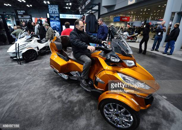 A visitor checks out CanAm Spyder motorcycle displayed at the Progressive International Motorcycle Show on December 13 2013 in New York The...