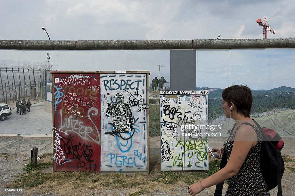 A visitor checks out the 'Wall on Wall' exhibition by German photographer Kai Wiedenhoefer, displayed on a remaining section of the Berlin wall July 26, 2013. Wiedenhoefer's 'Wall on Wall' project features giant panoramic photographs of walls taken in Northern Ireland, Iraq, Cyprus, the West Bank, Morocco, South Korea and the border between the United States and Mexico. The exhibition takes place between10 July and 13 September 2013.
