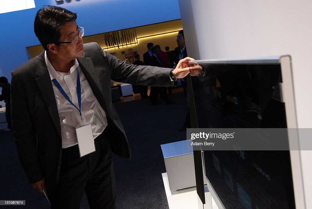 A visitor checks the thickness of a Loewe Individual ID television during the Internationale Funkausstellung (IFA) 2012 consumer electronics trade fair on August 31, 2012 in Berlin, Germany. Microsoft, Samsung, Sony, Panasonic and Philips are amongst many of the brands showcasing their latest consumer electronics hardware, software and gadgets to members of the public from August 31 to September 5.