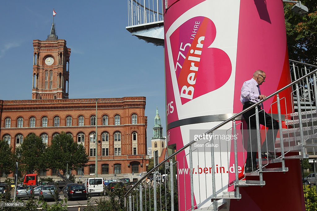 A visitor climbs an information tower that contains exhibits relating to the 775-year-history of Berlin as 19th-century Rotes Rathaus city hall stands nearby on August 29, 2012 in Berlin, Germany. The city of Berlin is currently holding a series of exhibitions and events ahead of its 775th anniversary, which it will celebrate at the end of October.