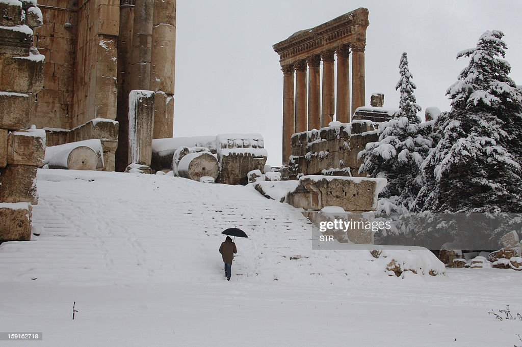 A visitor climbs the steps of Baalbek's Bachus temple as snow covers the Roman ruins of the historic town in eastern Lebanon's Bekaa Valley on January 9, 2013, following a fierce storm which has whipped the region this week with temperatures dropping dramatically and snow falling on low levels across Lebanon, Syria, Jordan and Israel.
