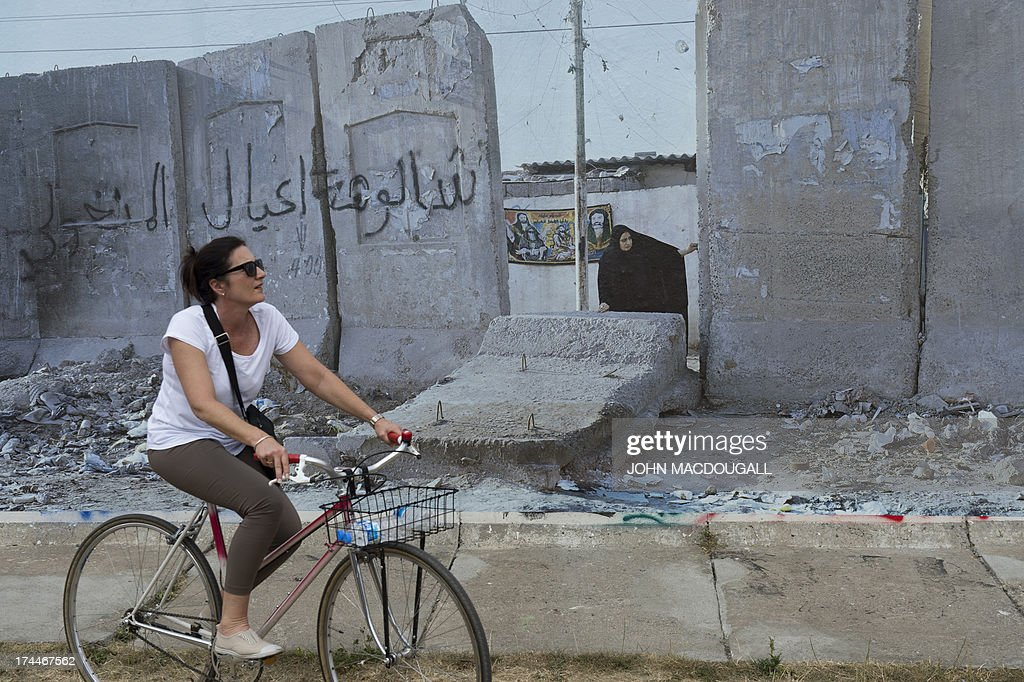 A visitor cycles past a giant photograph showing a wall at Sadr City, Baghdad, at the 'Wall on Wall' exhibition by German photographer Kai Wiedenhoefer, displayed on a remaining section of the Berlin wall July 26, 2013. Wiedenhoefer's 'Wall on Wall' project features giant panoramic photographs of walls taken in Northern Ireland, Iraq, Cyprus, the West Bank, Morocco, South Korea and the border between the United States and Mexico. The exhibition takes place between10 July and 13 September 2013.