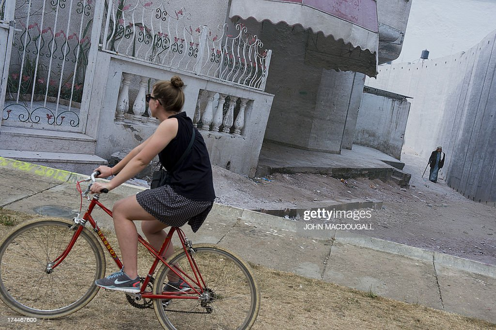 A visitor cycles past a giant photograph showing the 'security barrier' at the West Bank, at the 'Wall on Wall' exhibition by German photographer Kai Wiedenhoefer, displayed on a remaining section of the Berlin wall July 26, 2013. Wiedenhoefer's 'Wall on Wall' project features giant panoramic photographs of walls taken in Northern Ireland, Iraq, Cyprus, the West Bank, Morocco, South Korea and the border between the United States and Mexico. The exhibition takes place between10 July and 13 September 2013.