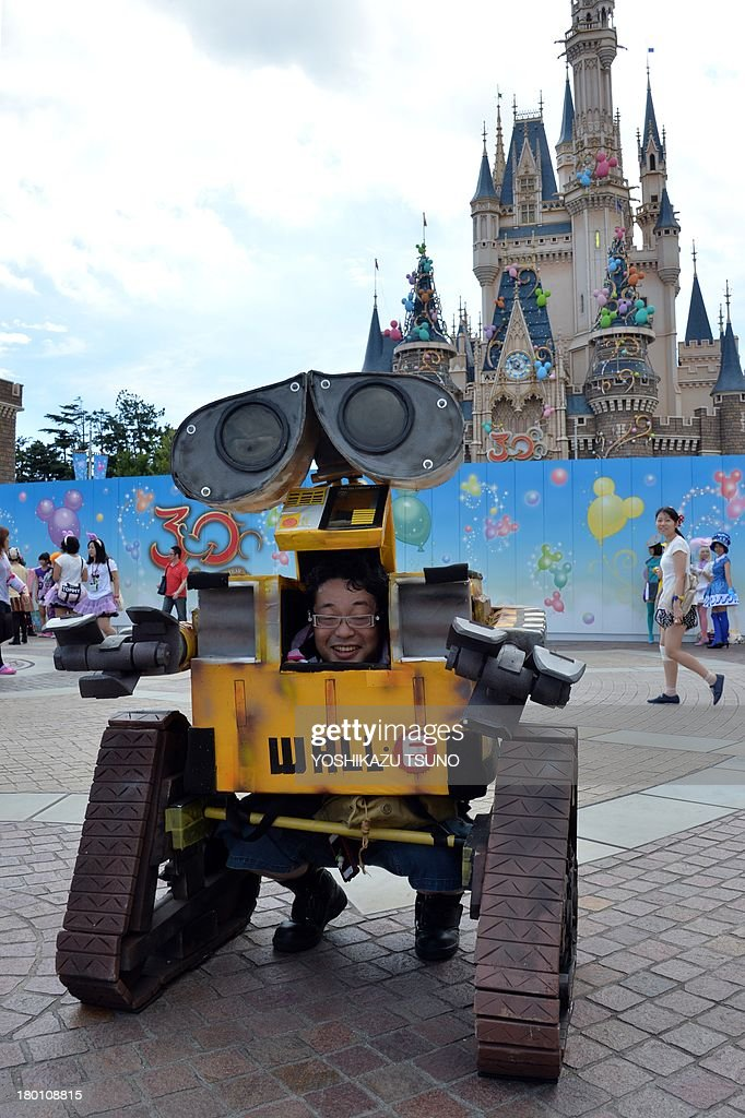 A visitor dressed in a costume from the Disney animated movie 'Wall-E' poses for a photo during a visit to Tokyo Disneyland in Urayasu, suburban Tokyo on September 9, 2013. Tokyo's Disney theme park runs Halloween events through till October 31 and visitors are allowed to wear Disney related costumes in the park. AFP PHOTO / Yoshikazu TSUNO