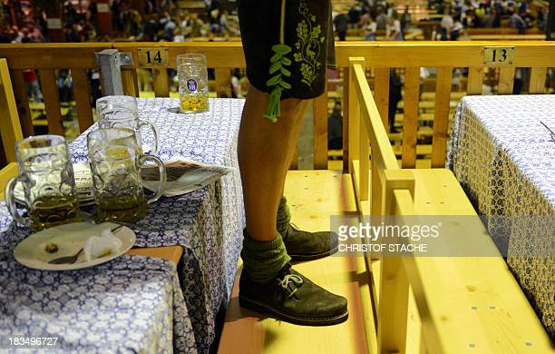 A visitor dressed in traditional Bavarian clothes stands at the bench beside of empty beer mugs in a festival tent of the Bavarian Oktoberfest beer...