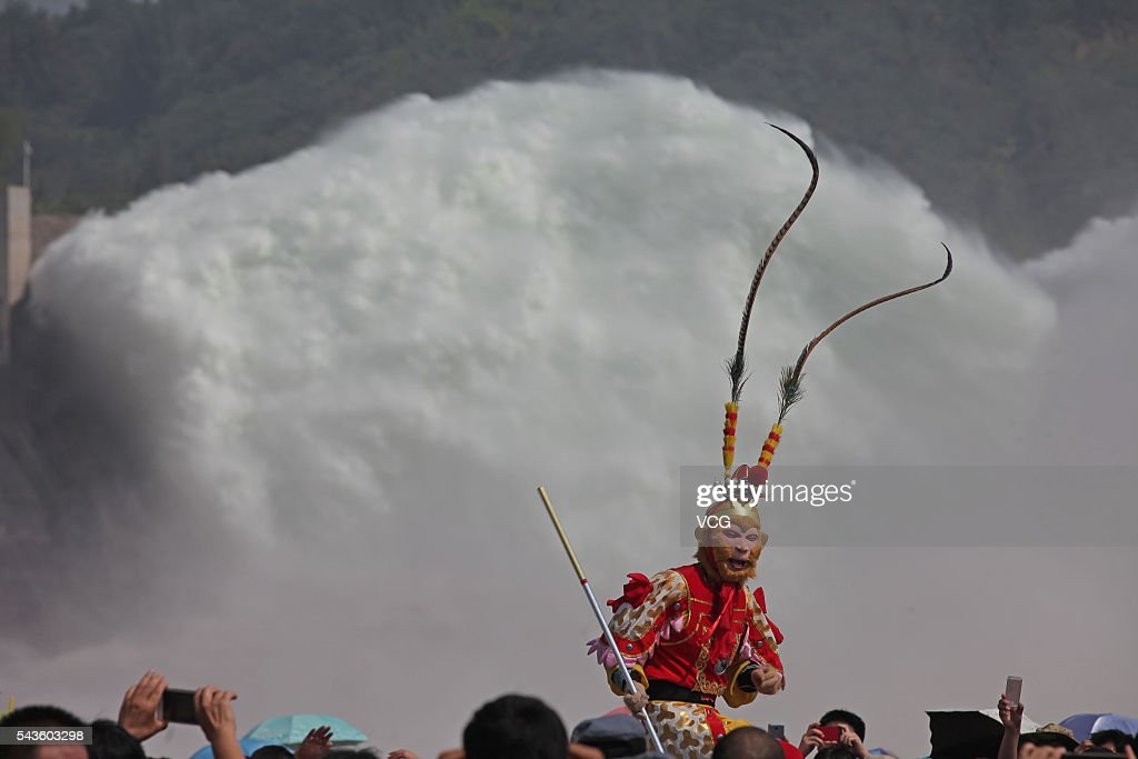 A visitor dresses himself as a Monkey King while viewing the water and sediment regulation with other visitors at Xiaolangdi Dam on the Yellow River on June 29, 2016 in Luoyang, Henan Province of China. The water and sediment regulation is to let sand, silt and other sediment rush with water out of the dam and flow into sea. The regulation can increase the dam's capacity of flood storage.
