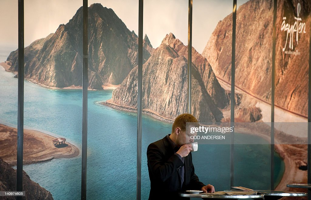 A visitor drinks a coffee standing in front of a giant poster advertising Egypt at the ITB international tourism fair at the fairgrounds in Berlin on March 9, 2012. The ITB travel trade show, with 10,644 exhibitors from 187 countries, is due to run until March 11.
