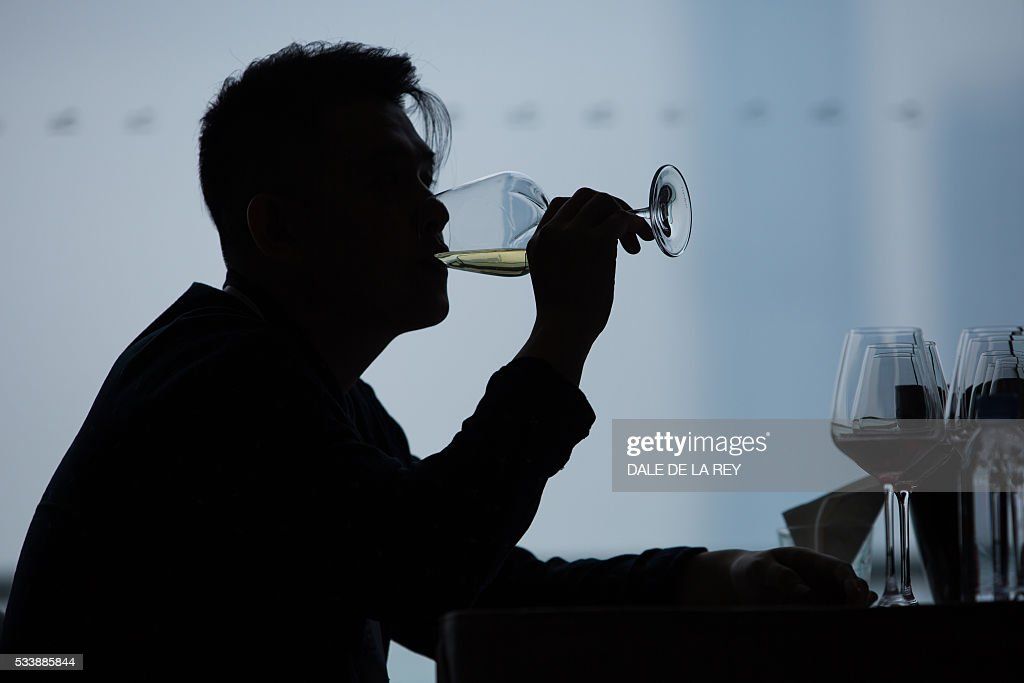 A visitor drinks a glass of wine during a tasting event at Vinexpo in Hong Kong on May 24, 2016. The international wine and spirits exhibition runs from May 24 to 26. / AFP / DALE