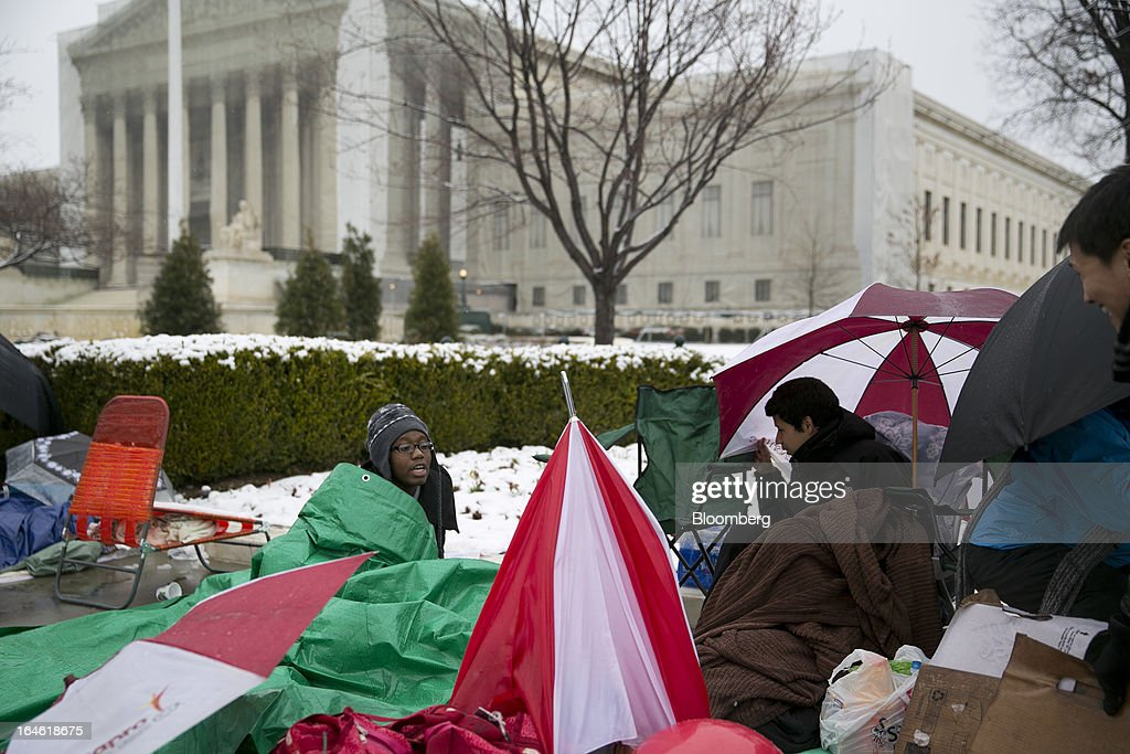 Visitor Ebony Miller, left, talks to fellow high school students while sitting underneath a tarp in line outside the Supreme Court building in Washington, D.C., U.S., on Monday, March 25, 2013. An early spring snowstorm tied up air traffic along the U.S. East Coast, threatening to bring 3 inches (7.6 centimeters) of slushy snow to the large cities from Washington to New York. Photographer: Andrew Harrer/Bloomberg via Getty Images
