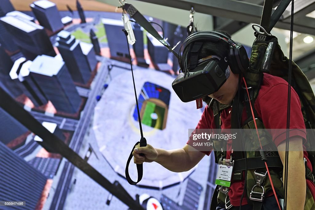 A visitor enjoys a visual reality (VR) headset simulating a parachutist during the annual Computex computer exhibition on May 31, 2016. More then 5,000 booths from thirty countries take part in COMPUTEX Show between May 31 to June 4. / AFP / SAM YEH