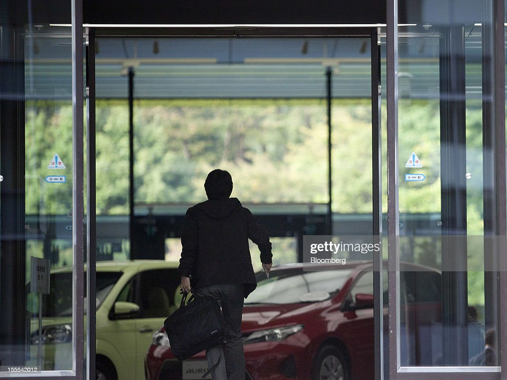 A visitor enters the Toyota Motor Corp. head offices in Tokyo, Japan, on Monday, Nov. 5, 2012. Toyota Motor Corp., Asia's biggest carmaker, raised its full-year profit forecast as rising demand for the Prius hybrid in the U.S. and Japan helped make up for slumping sales in China. Photographer: Tomohiro Ohsumi/Bloomberg via Getty Images