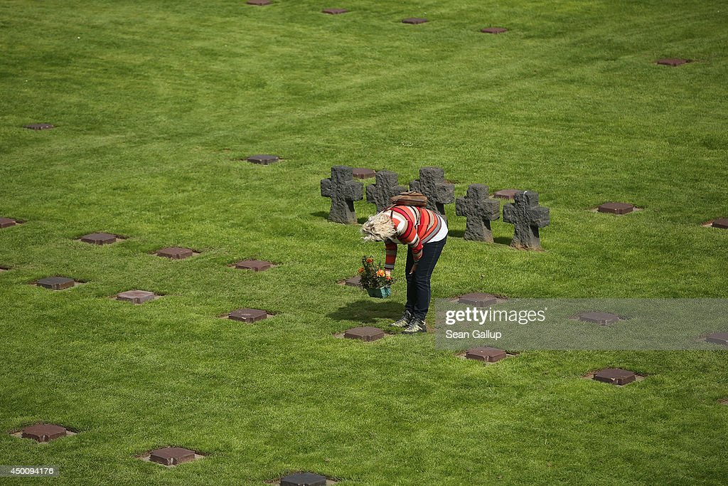 A visitor examines a gravestone at the German Cemetery where approximately 21,000 German World War II soldiers are buried on June 5, 2014 at La Cambe, France. Friday the 6th of June is the 70th anniversary of the D-Day landings that saw 156,000 troops from the Allied countries, including the United Kingdom and the United States, join forces to launch an audacious attack on the beaches of Normandy, these assaults are credited with the eventual defeat of Nazi Germany. A series of events commemorating the 70th anniversary are planned for the week with many heads of state travelling to the famous beaches to pay their respects to those who lost their lives.