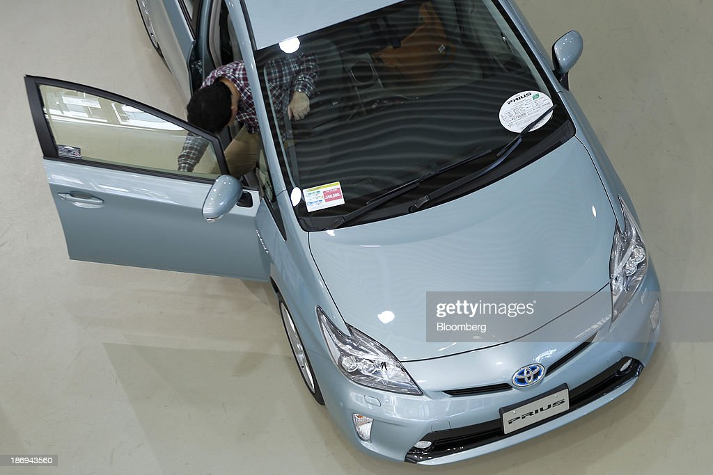 A visitor examines a Toyota Motor Corp. Prius vehicle displayed at the company's showroom in Tokyo, Japan, on Tuesday, Nov. 5, 2013. Toyota, the world's largest automaker, will probably deliver record semiannual profit when it reports earnings tomorrow, as the weaker yen bolsters the value of Japanese cars sold overseas. Photographer: Kiyoshi Ota/Bloomberg via Getty Images