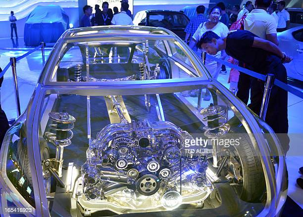 A visitor examines a transparent car scale model displayed at the auto show in Manila on April 4 2013 The annual auto show is being held from April 4...