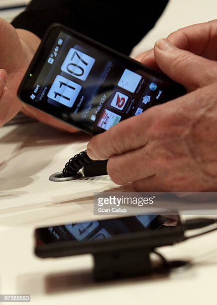 A visitor examines an HTC smartphone at the Vodafone stand at the CeBIT Technology Fair on March 3 2010 in Hannover Germany CeBIT will be open to the...