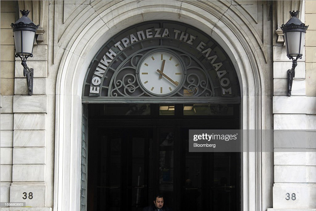 A visitor exits the offices of the National Bank of Greece in Athens, Greece, on Tuesday, Jan. 22, 2013. Euro-area finance ministers blessed the next disbursement of emergency aid for Greece, highlighting the goodwill that led to the unblocking of loans last month for Prime Minister Antonis Samaras's government. Photographer: Kostas Tsironis/Bloomberg via Getty Images