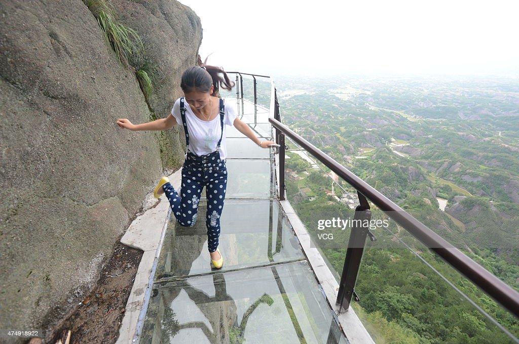 A visitor experiences a 180-meter long and 300-meter high musical glass plank road at Shiniuzhai scenic spot in Pingjiang County on May 27, 2015 in Yueyang, Hunan province of China. The plank road contains electronic components which produce sounds and different notes according to visitor's footsteps.