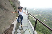 A visitor experiences a 180meter long and 300meter high musical glass plank road at Shiniuzhai scenic spot in Pingjiang County on May 27 2015 in...