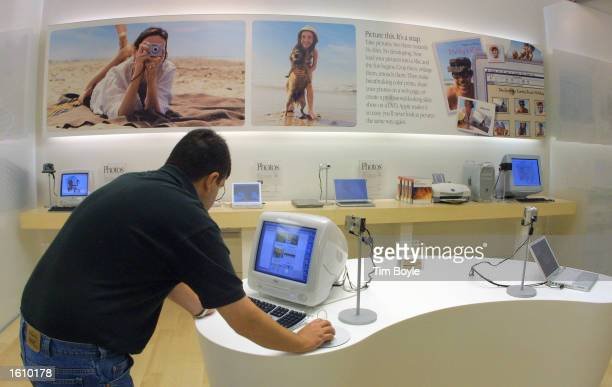 A visitor explores digital photography software as he works with a Macintosh computer during a media preview of a new Apple computer retail store...