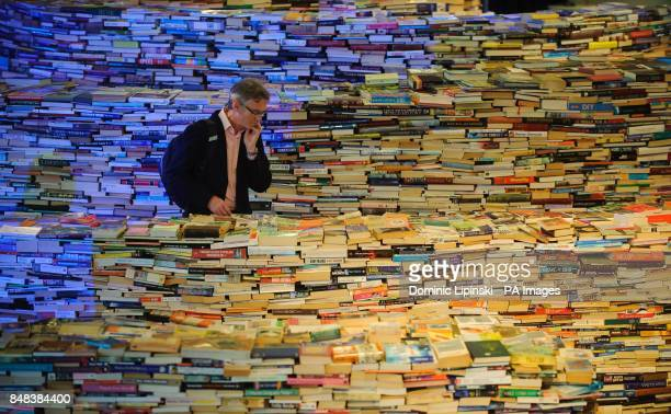 A visitor explores the 'aMAZEme' installation a maze constructed of 250000 books by Brazilian artists Marcos Saboya and Gualter Pupo at the Royal...