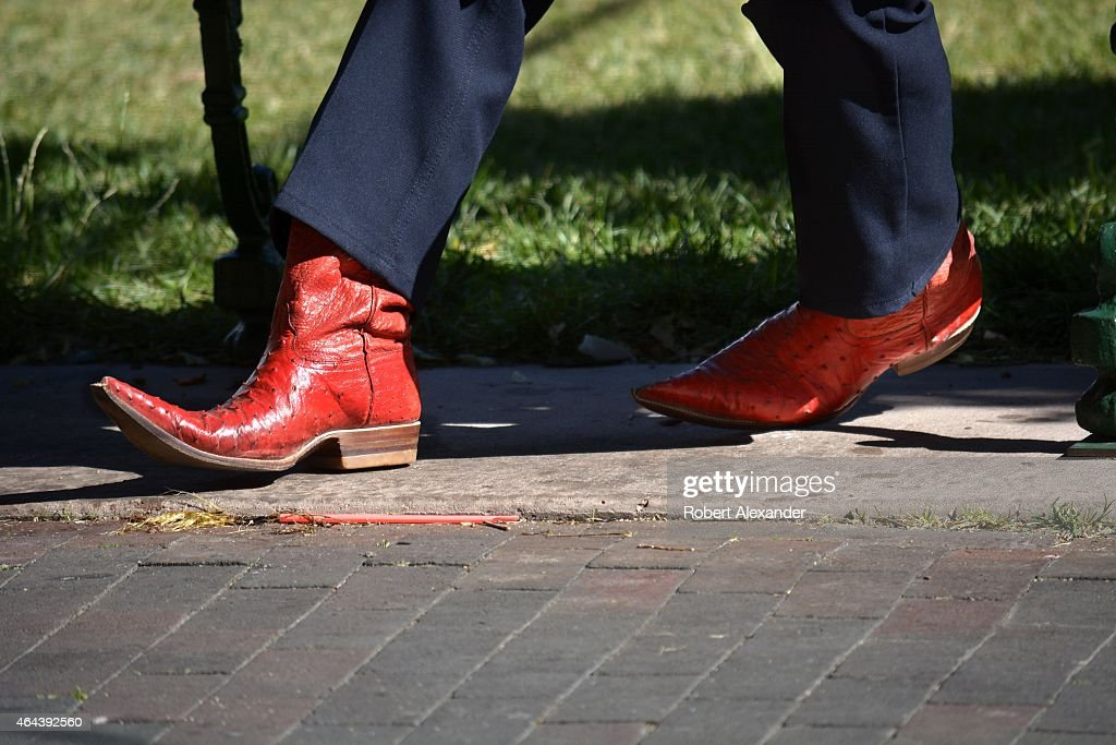 A visitor from Mexico carrying a guide book and wearing red Mexican pointy boots sits on a bench in the historic Plaza in Santa Fe New Mexico