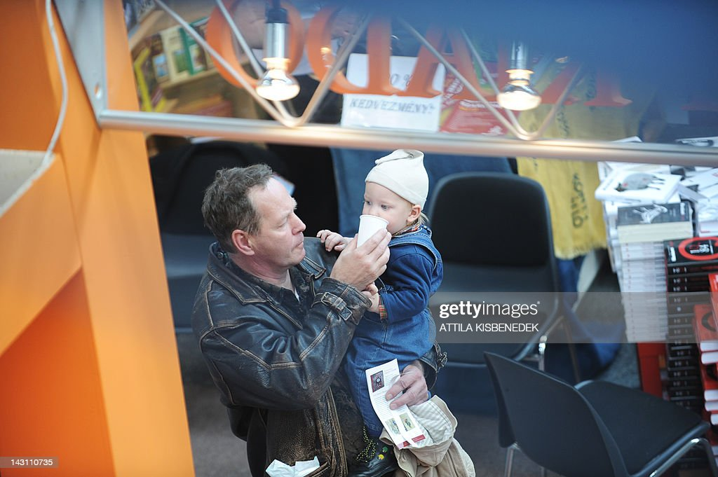 A visitor gives water to his son as he walks past stalls in the 19th International Book Festival (IBF), held in the Millenaris Culture Center in Budapest, on April 19, 2012. Budapest's 19th International Book Festival, one of the biggest in central Europe, opened today featuring popular Nordic writers as this year's guests of honour. More than 20 northern European writers will attend the four-day event in the Hungarian capital, including award-winning Swedish crime novelist Hakan Nesser, Norway's Jostein Gaarder, Danish author Janne Teller and Leena Lehtolainen from Finland.