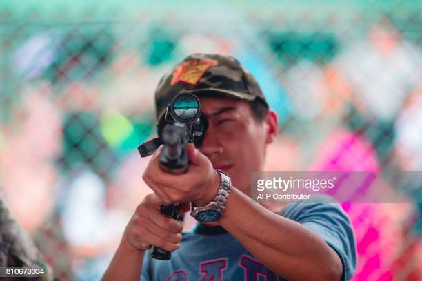 A visitor handles a Type 88 sniper rifle on display at the Ngong Shuen Chau naval base on Stonecutters Island in Hong Kong on July 8 during the PLA...