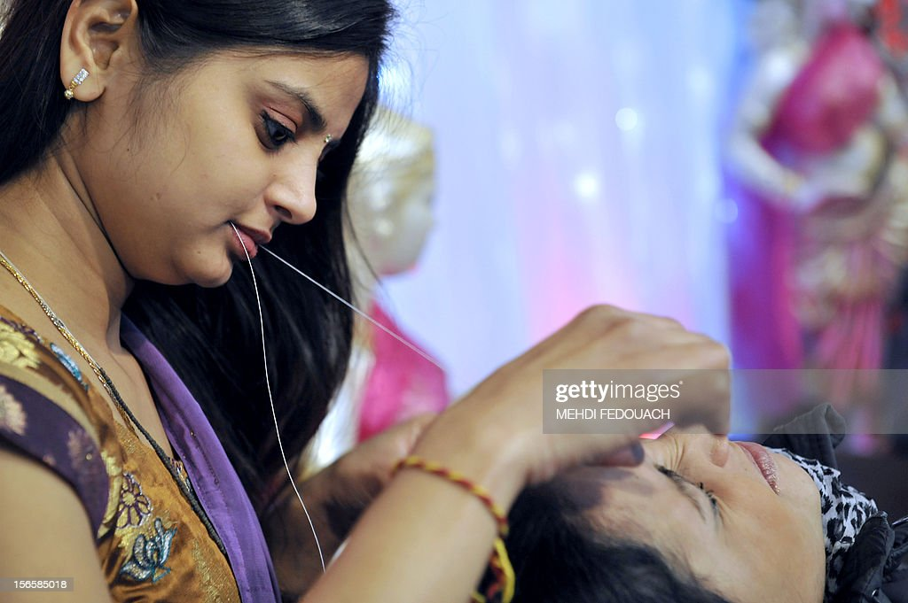 A visitor has her eyebrows made with a thread by an Indian woman at a stand during the Oriental Wedding Fair in Paris on November 17, 2012. The event runs until November 18.