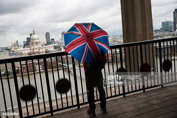 A visitor holding a Union Jack umbrella looks out to St Paul's Cathedral from the 10th floor viewing platform at the Tate Modern's new Switch House...