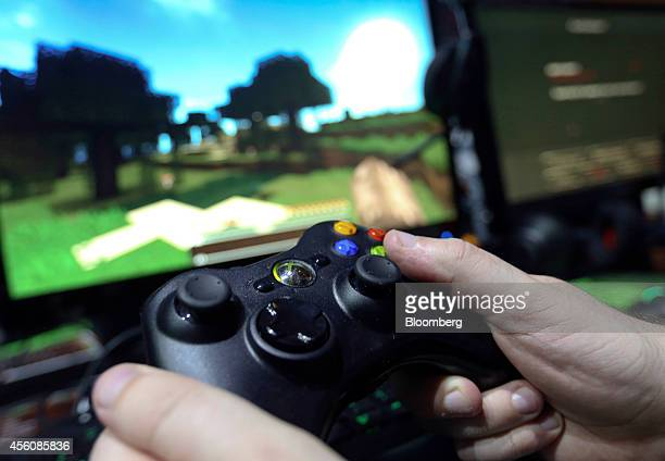 A visitor holds a hand control unit as he plays the Minecraft computer came produced by Mojang AB on a Microsoft Corp Xbox One games consoles during...