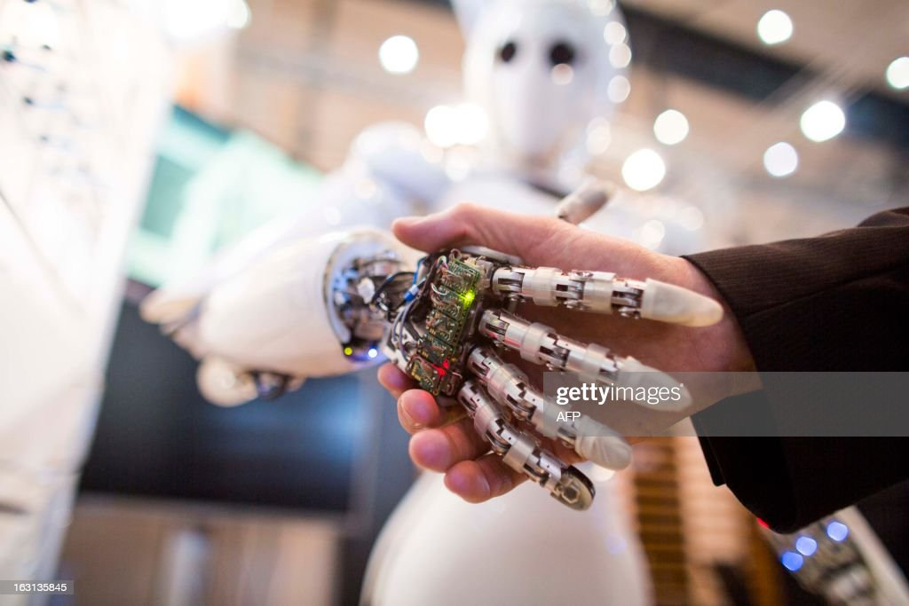 A visitor holds a hand of AILA, or Artificial Intelligence Lightweight Android, during a demonstration at the German Research Center for Artificial Intelligence GmbH (Deutsches Forschungszentrum fuer Kuenstliche Intelligenz GmbH) stand at the 2013 CeBIT technology trade fair on March 5, 2013 in Hanover, Germany. CeBIT will be open March 5-9.