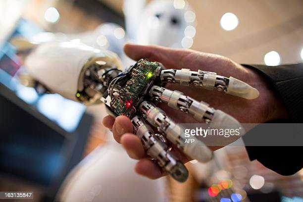 A visitor holds a hand of AILA or Artificial Intelligence Lightweight Android during a demonstration at the German Research Center for Artificial...