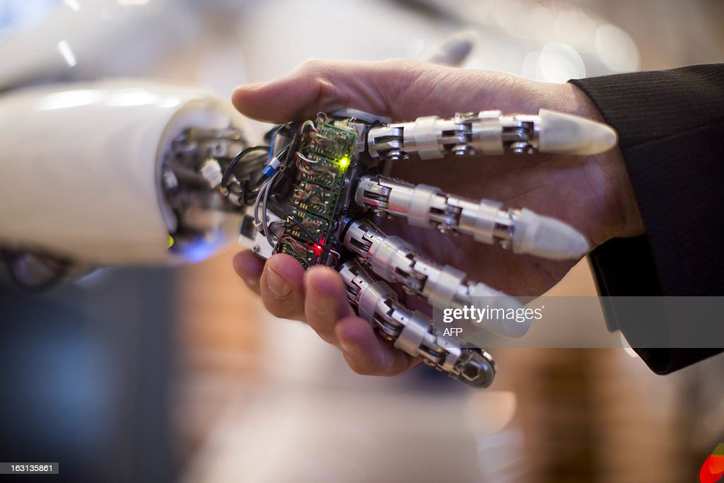 A visitor holds a hand of AILA, or Artificial Intelligence Lightweight Android, during a demonstration at the German Research Center for Artificial Intelligence GmbH (Deutsches Forschungszentrum fuer Kuenstliche Intelligenz GmbH) stand at the 2013 CeBIT technology trade fair on March 5, 2013 in Hanover, Germany. CeBIT will be open March 5-9. AFP PHOTO / CARSTEN KOALL