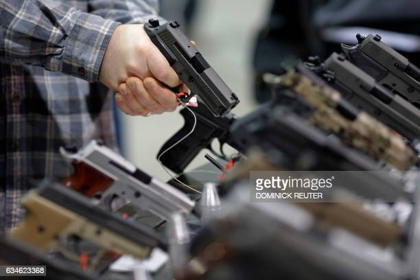 A visitor holds a pistol at a gun display during a National Rifle Association outdoor sports trade show on February 10 2017 in Harrisburg...