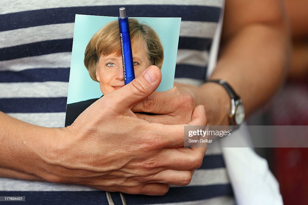 A visitor holds a postcard that shows German Chancellor Angela Merkel before asking her for her autograph during the annual open-house day at the Chancellery on August 25, 2013 in Berlin, Germany. Germany is facing federal elections scheduled for September 22 and so far the CDU has a substantial lead in polls over the opposition.