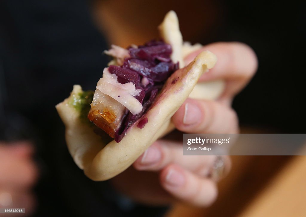 A visitor holds a steamed bun of maple-glazed pork belly with pickled red cabbage on the first day of Street Food Thursday at the Markthalle Neun market hall in Kreuzberg district on April 11, 2013 in Berlin, Germany. Street Food Thursday features sidewalk delicacies from a variety of culinary traditions and will be open every Thursday from 5 until 11. Berlin has become a major tourist destination in Europe and has developed a reputation as a hip, affordable and open-minded city.