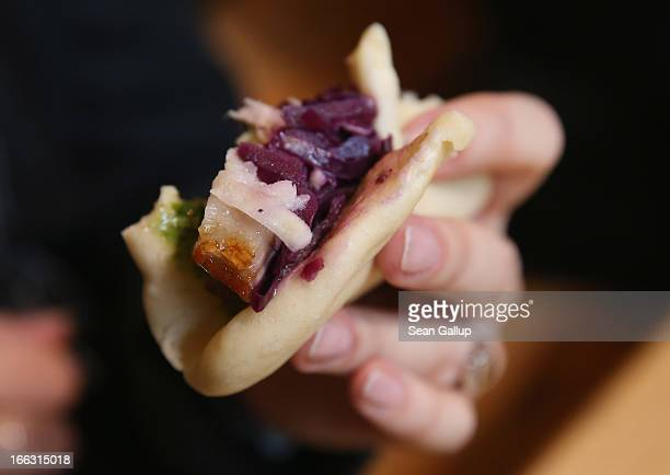 A visitor holds a steamed bun of mapleglazed pork belly with pickled red cabbage on the first day of Street Food Thursday at the Markthalle Neun...