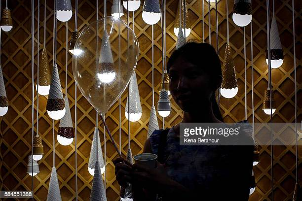 A visitor holds an edible balloon at the Museum of Ice Cream across from the Whitney Museum on July 29 2016 in New York City The temporary museum...