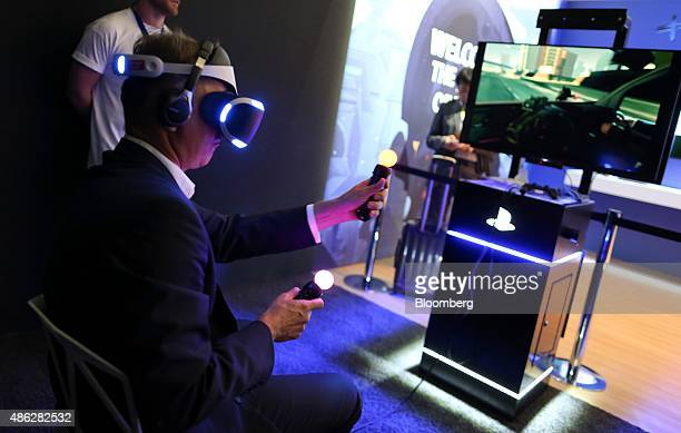 A visitor holds illuminated controllers while wearing a prototype of the Sony Project Morpheus virtual reality gaming headset at the Sony Corp...