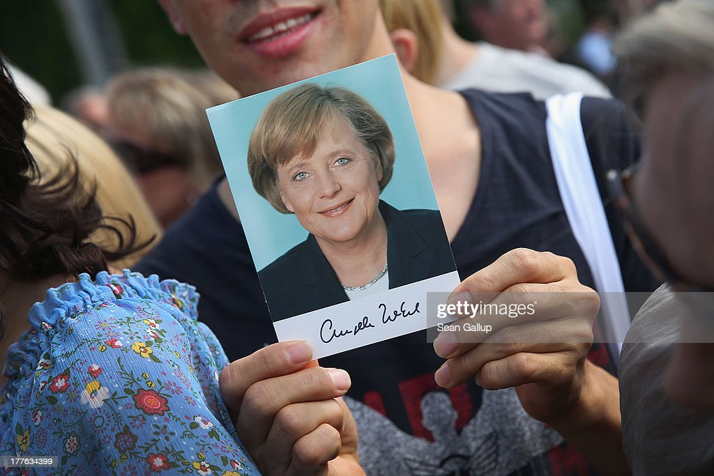 A visitor holds up a postcard that shows German Chancellor Angela Merkel during the annual open-house day at the Chancellery on August 25, 2013 in Berlin, Germany. Germany is facing federal elections scheduled for September 22 and so far the CDU has a substantial lead in polls over the opposition.