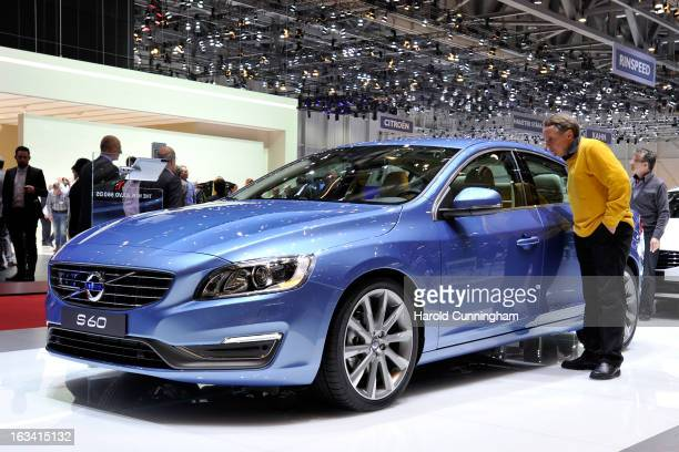 A visitor inspect a Volvo S60 during the 83rd Geneva Motor Show on March 6 2013 in Geneva Switzerland Held annually with more than 130 product...
