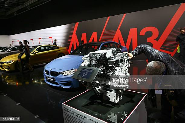 A visitor inspects a BMW M TwinPower Turbo motor on display at the Bayerische Motoren Werke AG stand at the Moscow International Auto Salon in Moscow...
