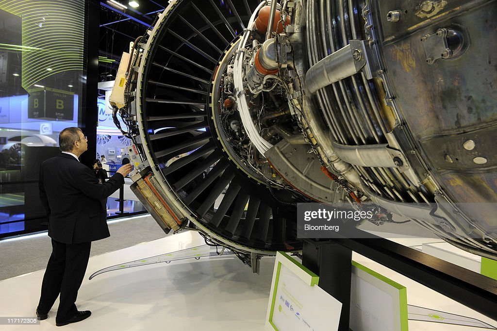 A visitor inspects a GEnx aircraft jet engine, manufactured by General Electric Co., at the company's stand at the Paris Air Show in Paris, France, on Thursday, June 23, 2011. The 49th International Paris Air Show, the world's largest aviation and space industry show, takes place at Le Bourget airport June 20-26. Photographer: Fabrice Dimier/Bloomberg via Getty Images