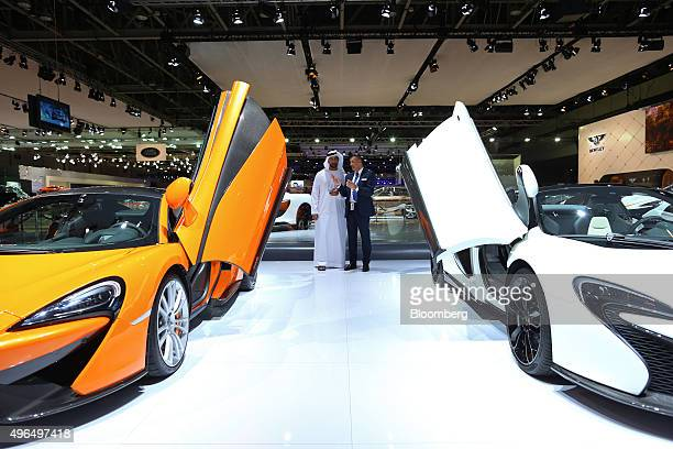 A visitor inspects an orange McLaren 570S and a McLaren 650S Spider Al Sahara 79 super car manufactured by McLaren Automotive Ltd as it sits on...
