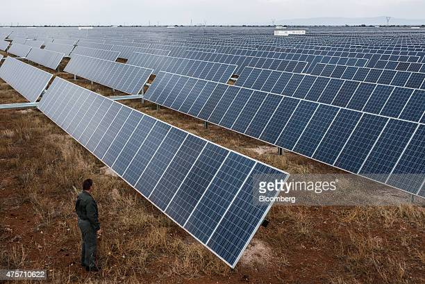 A visitor inspects photovoltaic panels operating in the Sishen solar park operated by Acciona SA in Kathu Northern Cape South Africa on Tuesday June...