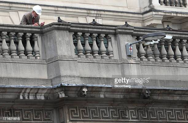 A visitor inspects the guttering from a balcony at the Bank of England in the City of London UK on Thursday June 27 2013 Incoming Bank of England...